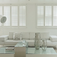 Soft white shutters create an effortlessly cool style