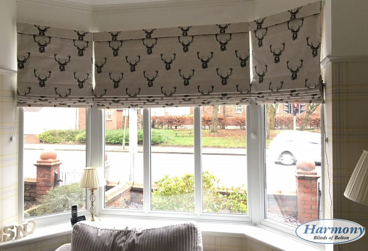 Patterned roman blinds in a bay window harmony blinds of for Roman shades for bay window