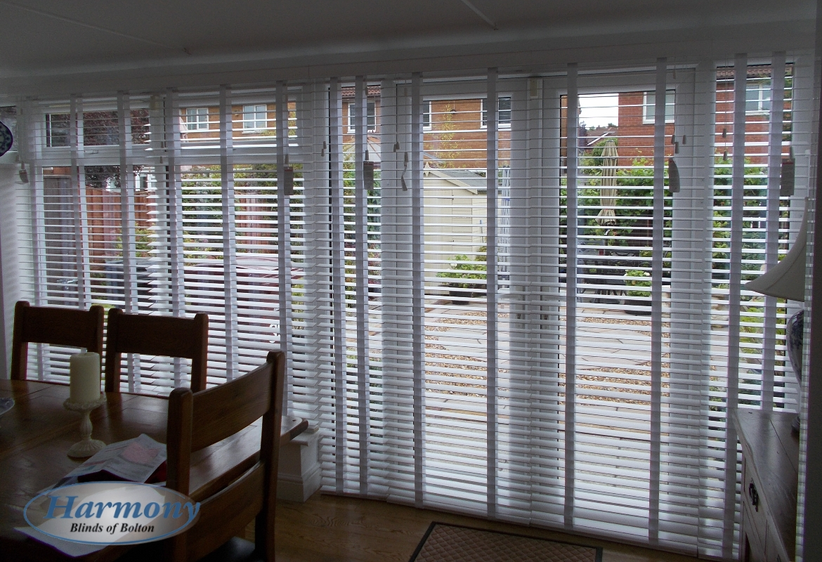 White Wooden Blinds With Tapes Covering Patio Doors