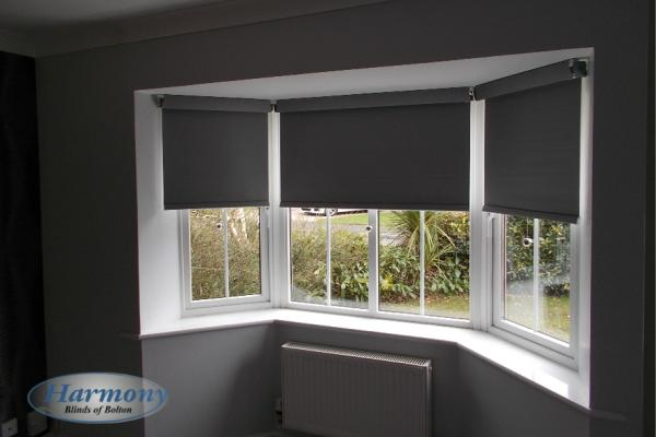 Grey 'Senses' Roller Blinds with Chrome finishes in a Bay Window