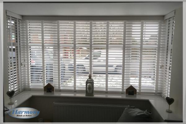 White FauxWood Blinds with Ladder Tapes in a Bay Window