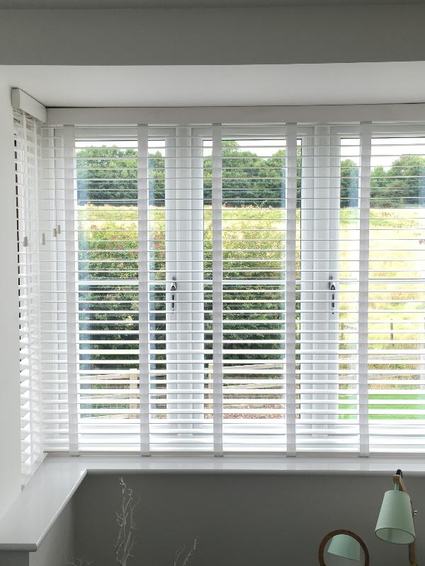 White Wooden Blinds with Tapes in a box Bay Window